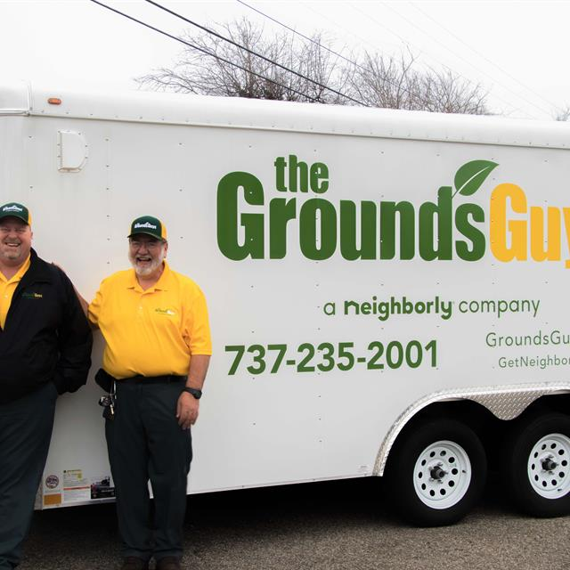 The Grounds Guys of Pflugerville in front of trailer