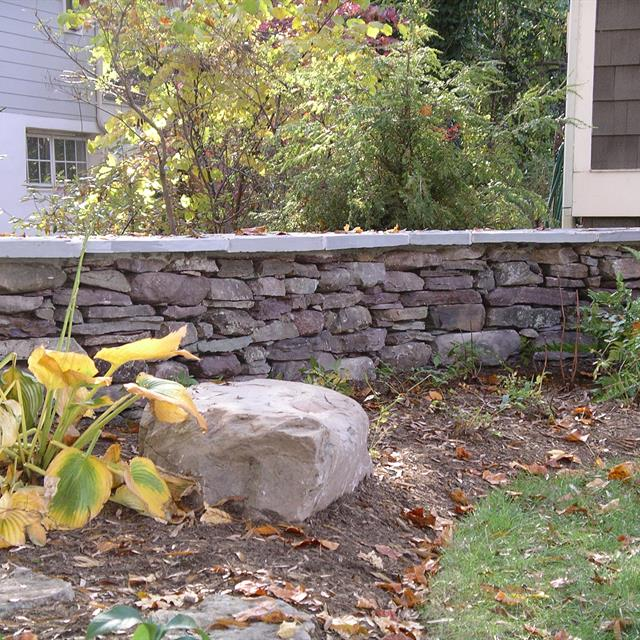 short wall made of stones  framing a yard