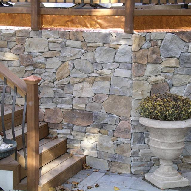 stone work on wall with attached stairs and a planter