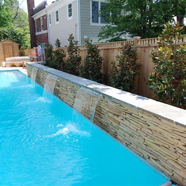 swimming pool with stonework wall fountain pring into it