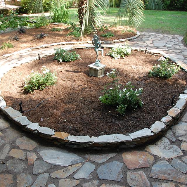 circular stonework with rosebushes