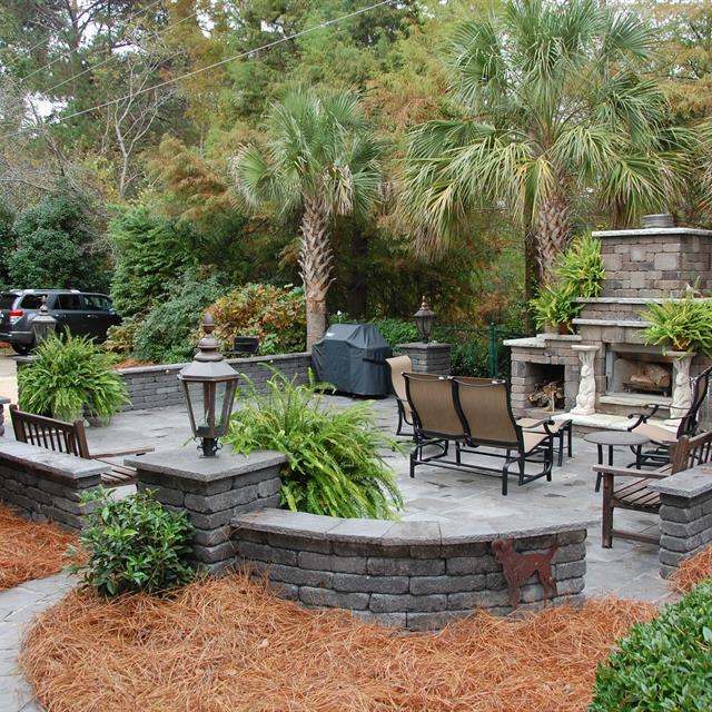 mulch and tropical plants landscapting with stone patio hardscaping with firepit.