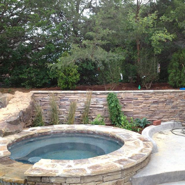 Stone wall with concrete and stone hottub