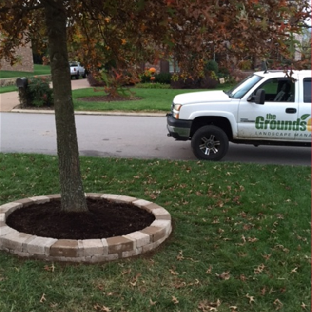 Grass with stone planter and tree with the Ground Guys truck