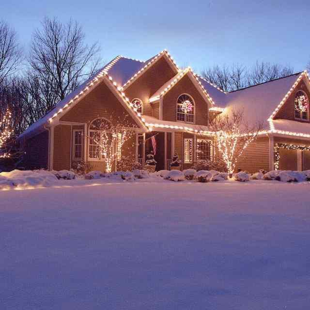 Snow in front of house with holiday lighting