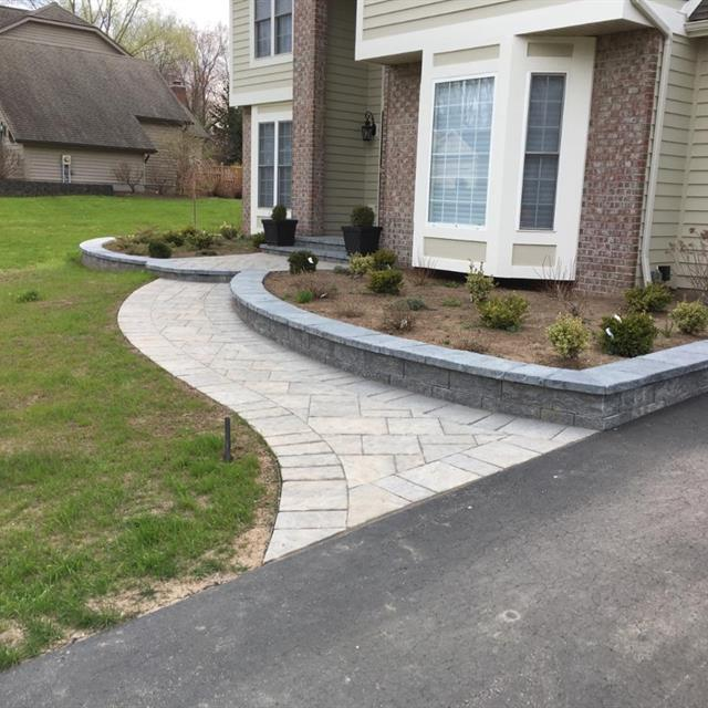 stone walkway lined by grass on the left and a planter on the right leading to house