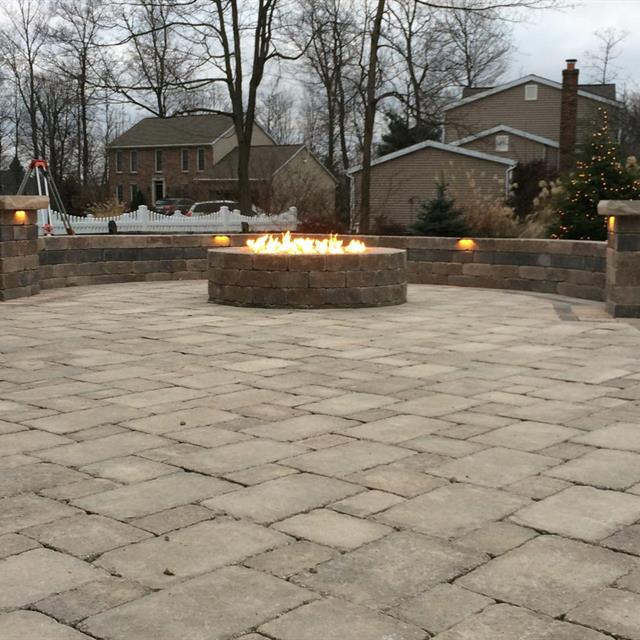 stone patio and lit firepit with short wall