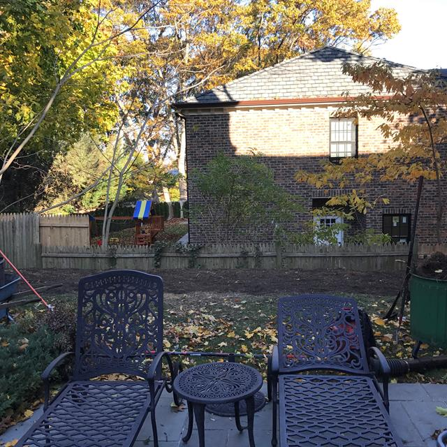 Outdoor patio with furniture surrounded by a backyard with lots of leaves on the ground.