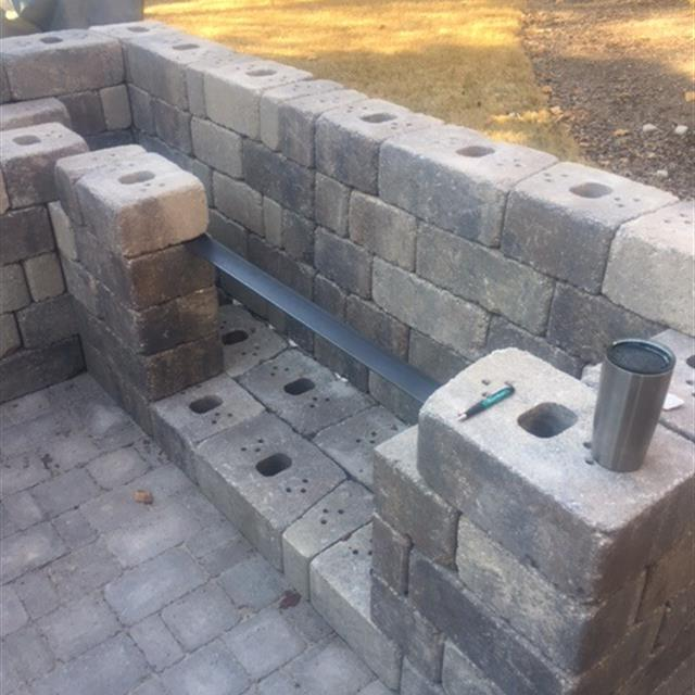 cement pavers being stacked and fitted with rebarfor a nice solid outdoor grill area for a residence