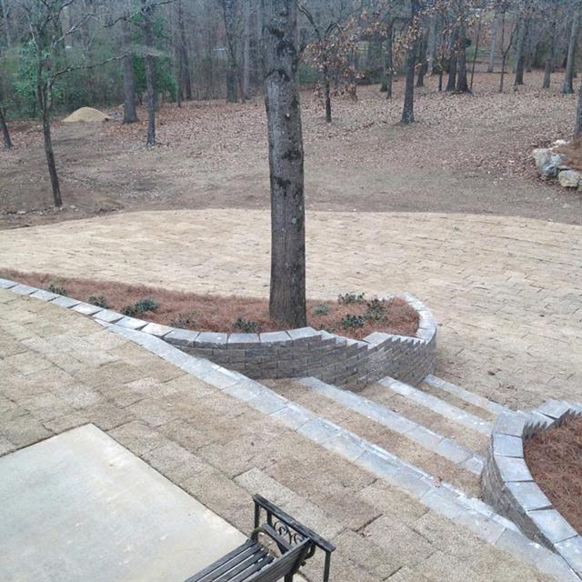 New natural color stone hardscape laid down that leads nicely to a forest of trees in their natural state