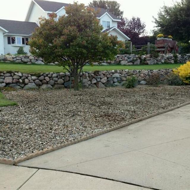 Stone retaining wall and well manicured lawn