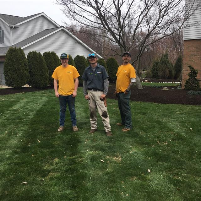 Well manicured lawn and Grounds Guys workers