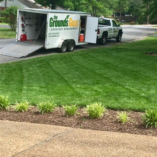 Grounds Guys truck, trailer and well manicured lawn