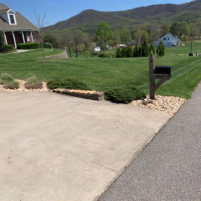 grass lawn and driveway with home and a mailbox