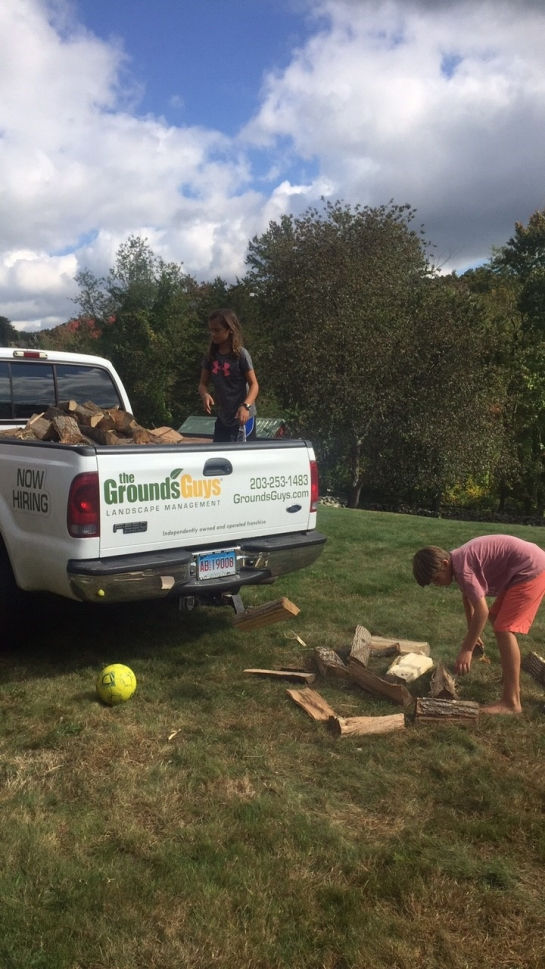 Children loading the Grounds Guys truck with wood