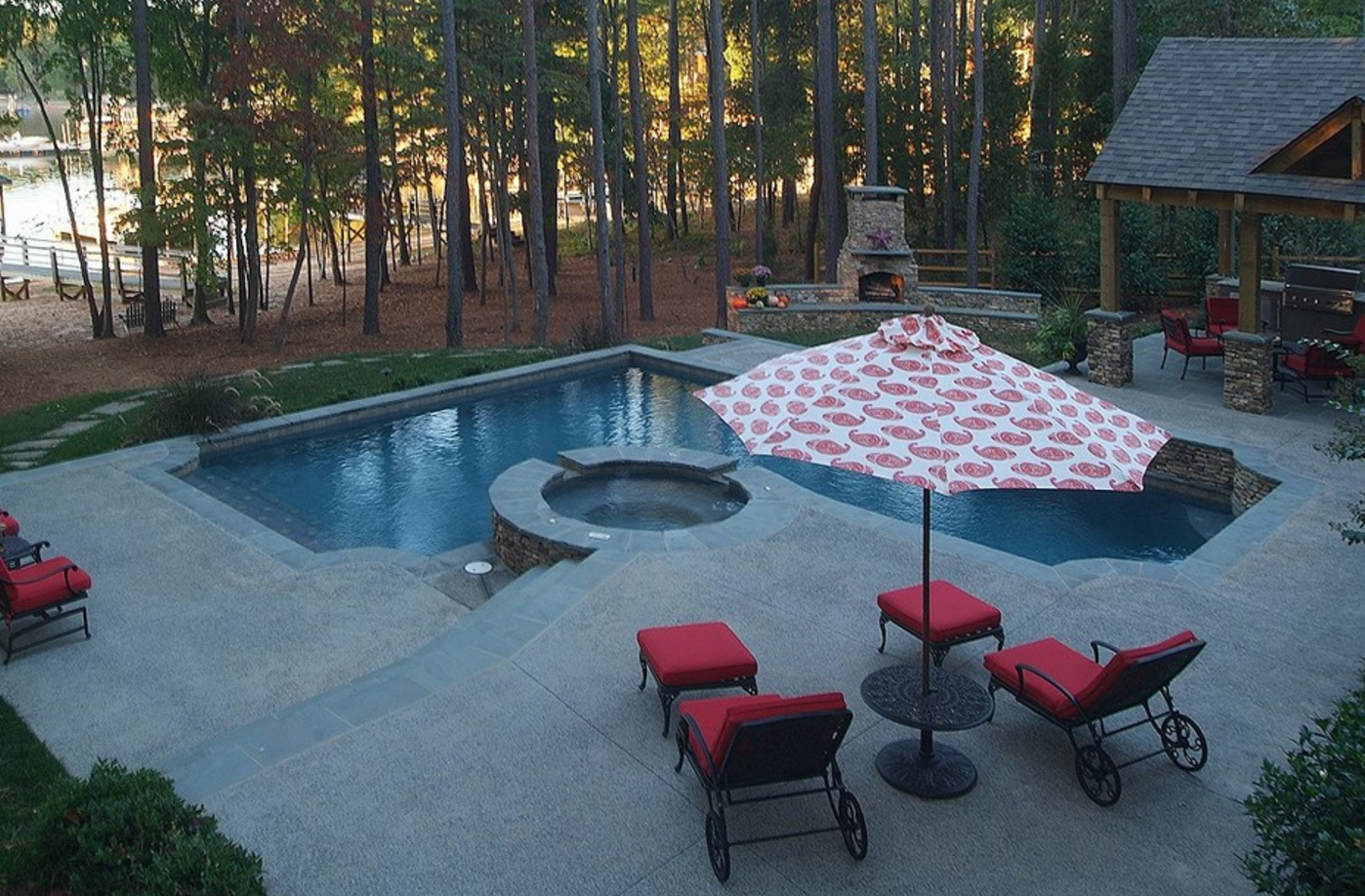 Poolside patio with fireplace and red furniture