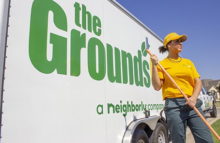 woman wearing The Grounds Guys uniform standing in front of trailer