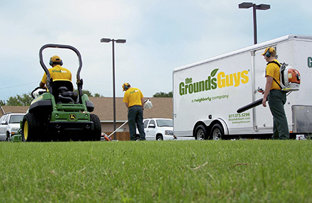 The Grounds Guys employees performing lawn work