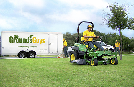 The Grounds Guys employee using industrial lawn mower