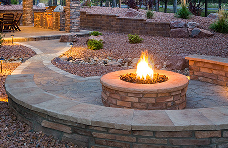lit stonework fire pit with built-in wrap-around bench
