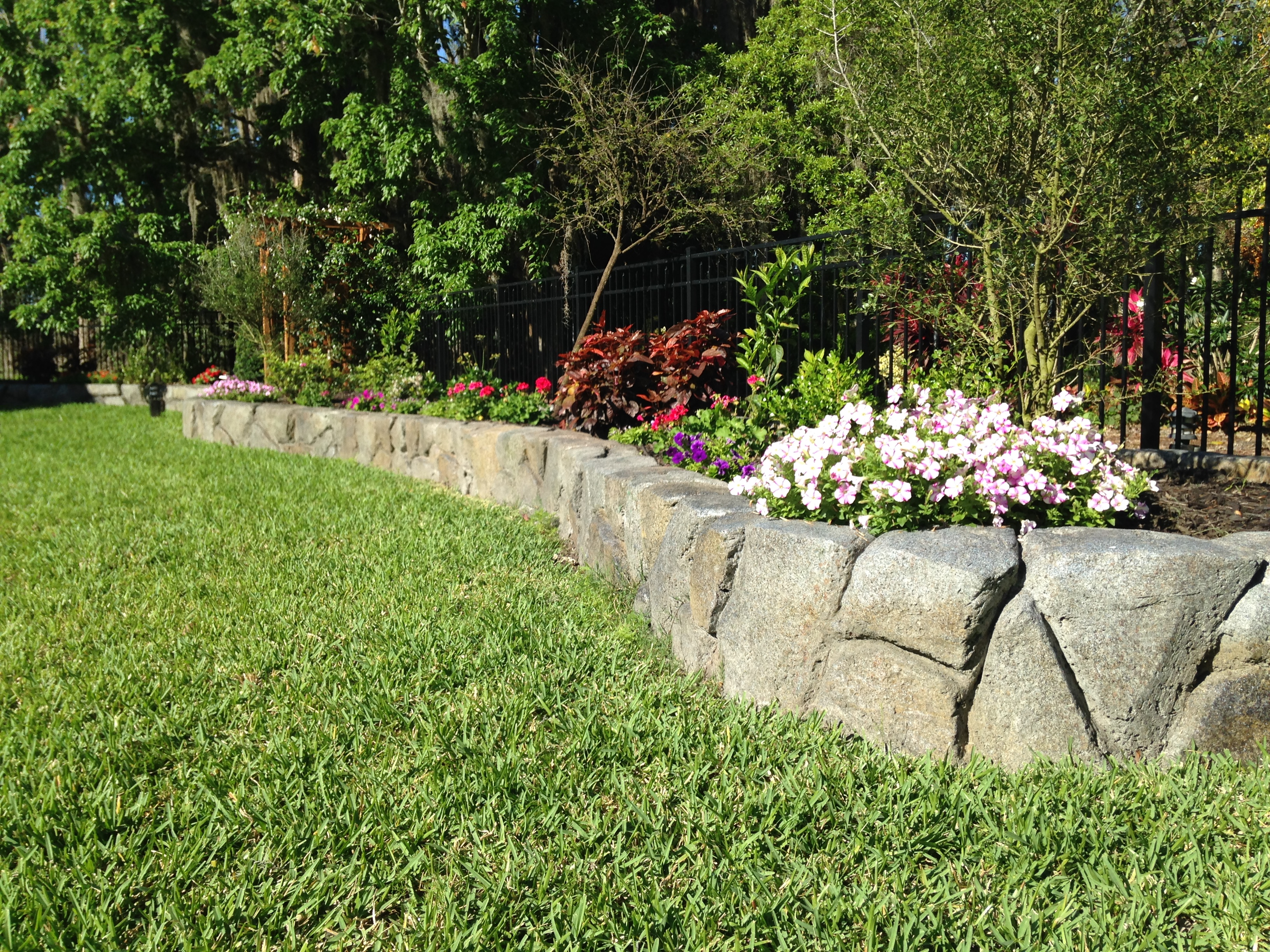 Landscaped stonework wall with green lawn